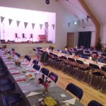 Tables set for a meal in Ashurst village Hall