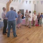 People at an event in Ashurst Village hall, which is decorated with bunting