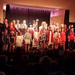 The cast of the 2019 pantomime singing on the stage together
